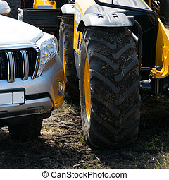 Farmer's tractor and a luxury SUV side by side  in dirt on the field
