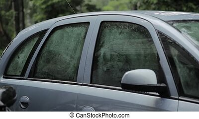 Rain falling on car side, roof and glass. Fogged glass -...