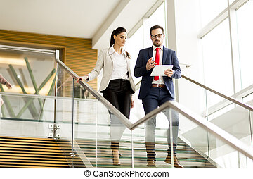 Young businesswoman and businessman walk down stairs in...