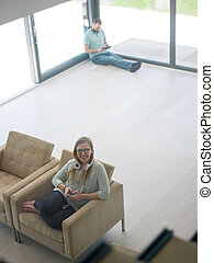 woman using mobile phone - young happy woman sitting on sofa...