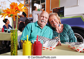 Smiling elderly couple eating out from a food truck