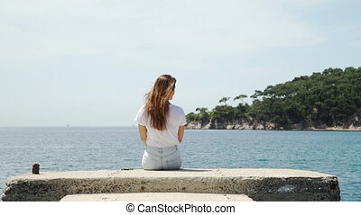 Woman relaxes by lake sitting on the edge of pier