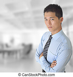 Young business man of Asian looking at you in office