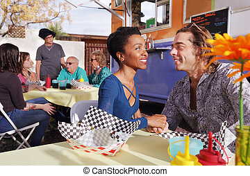 Diverse couple smiles at one another while seated