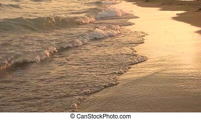 Seashore in slow-mo. Small waves at sunset.