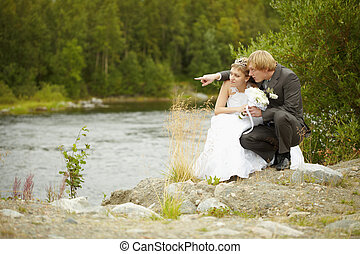Bride and groom sit on riverbank - The bride and groom sit...
