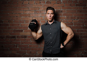 Muscular guy doing exercises with dumbbell against a brick...