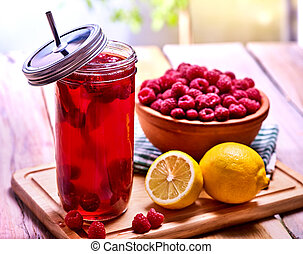 Cold non alcoholic cocktail with lemon half and raspberries...