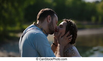Young caucasian couple pose to photographer near the water....