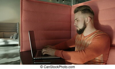 Bearded man sitting on couch with laptop