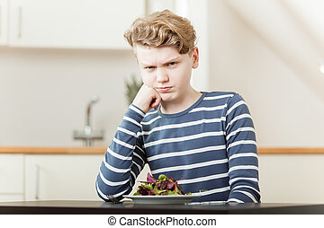 Pouting boy sitting in front of salad greens - Pouting boy...