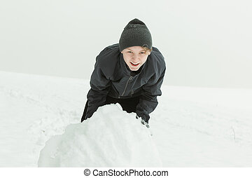 Laughing boy rolling a large snowball outside - Single...
