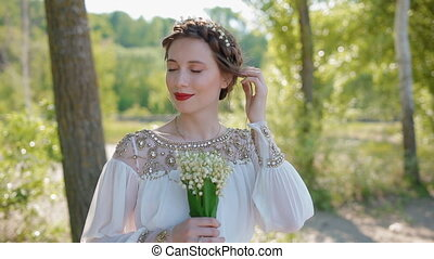 Portrait of woman with lilies of the valley in her hands....