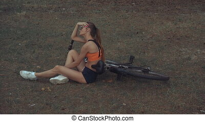 young tired girl with a Bicycle resting