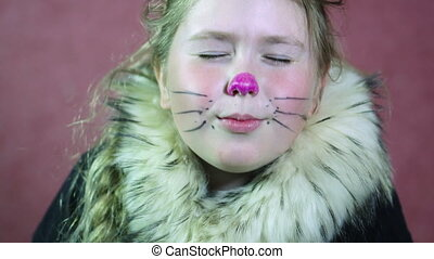 Little girl dressed a cat costume Draw a mustache and nose....