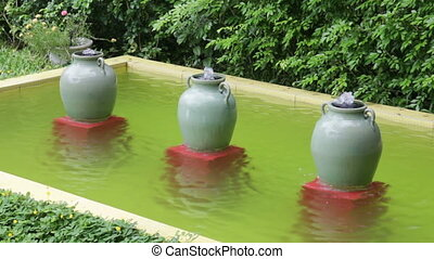 Ceramic water-filled jars decorated in outdoors garden,...