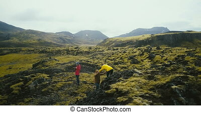 Aerial view of group of tourists hiking on lava fields in...