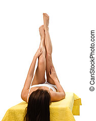Female legs - long legs of relaxed lady with yellow towel...