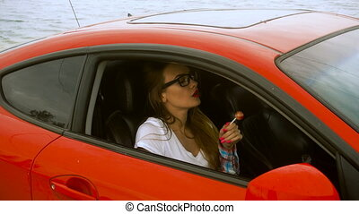 sexy lady in glasses sits in a red sport car and licks a...