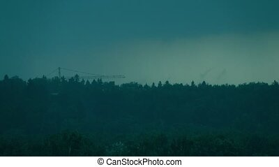 Time lapse of moving heavy rain storm. Distant construction crane and forest trees