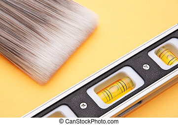 Home Improvement Scene.  Paintbrush and Level on Yellow.