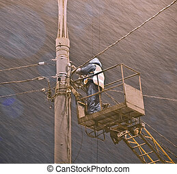 Snowstorm vs lineman - lineman in cradle at bad weather