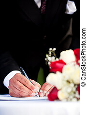 Signature - A groom signing his wedding license Focus on...