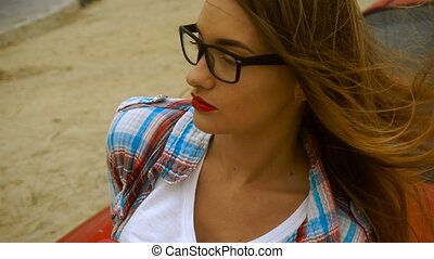 blonde with red lips wears a glasses and licks a lollipop -...
