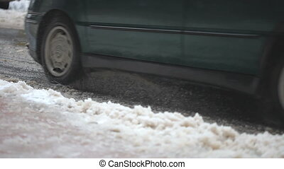 Car driving on the snow wet street