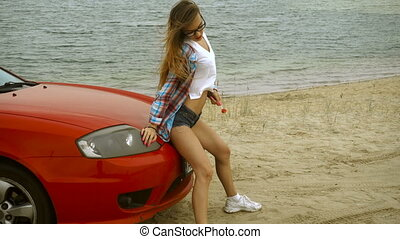 gorgeous slim lady sits on a red car on a beach - gorgeous...