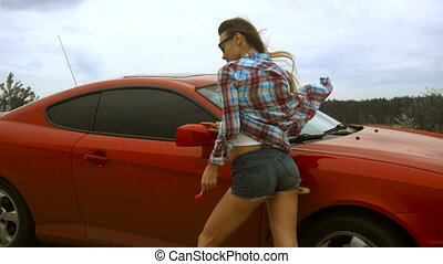 young sexy blonde stands with a red car and licks a lollipop...