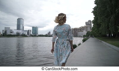 Anonymous woman on embankment in gloomy day