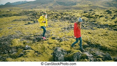 Copter flying around two woman on lava field in Iceland....
