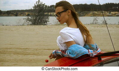 attractive lady with red lips and sunglasses licks a...