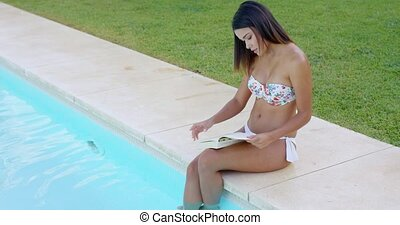 Young woman reading a book at the swimming pool - Young...