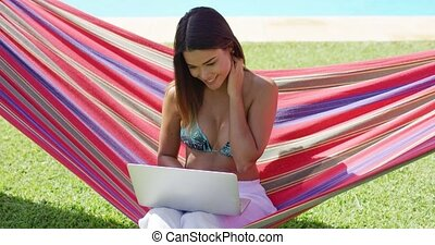 Happy woman using laptop in hammock - Single smiling woman...