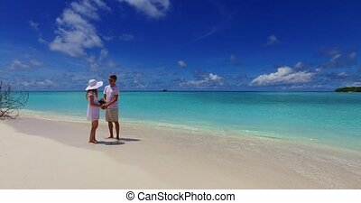 Maldives white sandy beach 2 people a young couple man woman standing together in love on sunny tropical paradise island with aqua blue sky sea water ocean 4k