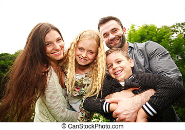 Closeup portrait of happy smiling family in city park