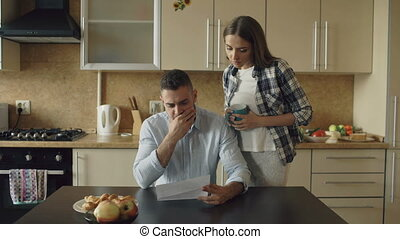 Uspet young man reading unpaid bills and hugged by his wife supporting him in the kitchen at home