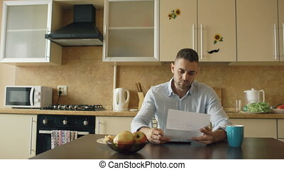 Uspet young man reading letter with unpaid bill in the kitchen at home
