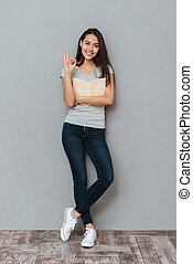 Smiling cute young woman holding book and showing ok gesture...