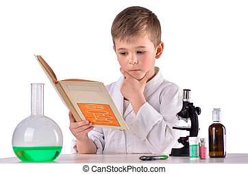 Thoughtful science boy reads book at chemistry lab at the desk