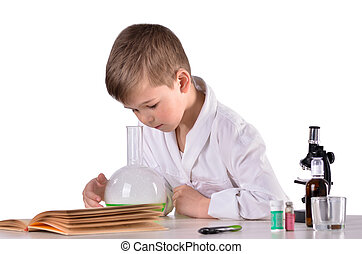 Science boy looks inside flask at the desk