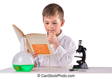 Science boy reads book at chemistry lab at the desk