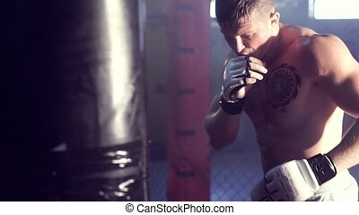 Boxer and punching bag - Young male boxer hitting punching...