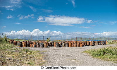 Rusty fuel and oil casks stored at an fence