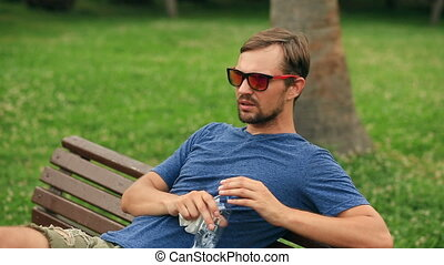A man sits on a bench in a city park and is exhausted from the heat.