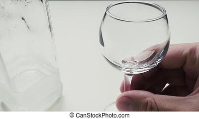 Man pours himself a glass of vodka - A man pours himself a...