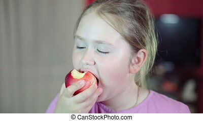 Caucasian white child eats a nectarine and smiling at the camera. 4K