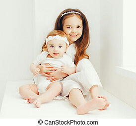 Two cute sisters children together at home in white room near window